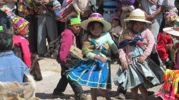 Die Mädchen und Jungen tanzen in ihren traditionellen Kostümen